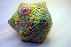 Knitted wool mathematical designer toy. Coloful knitted yarn polygon figure Macro detail Royalty Free Stock Photo