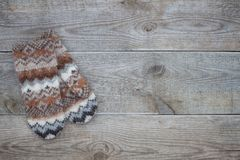 Knitted brown wool mittens on old wooden background with copy space. Knitted wool mittens on old wooden background with copy space. Rustic Royalty Free Stock Image