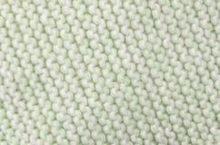 Knitted wool scarf fabric texture background. Seamless knitted green and white wool scarf background. Neutral winter fabric  texture Stock Photography