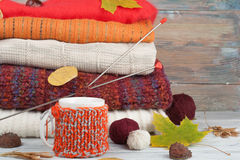 Knitted wool sweaters. Pile of knitted winter, autumn clothes on red, wooden background, sweaters, knitwear, ball, cup Royalty Free Stock Photo