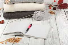 Knitted wool sweaters. Pile of knitted winter, autumn clothes on wooden background, sweaters, knitwear, pen, book, space. For text royalty free stock image