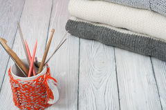 Knitted wool sweaters. Pile of knitted winter, autumn clothes on wooden background, sweaters, knitwear, pen, cup, space. For text royalty free stock photography