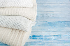 Knitted wool sweaters. Pile of knitted winter clothes on blue wooden background, sweaters, knitwear, space for text. Knitted wool sweaters. Pile of knitted stock image