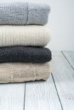 Knitted wool sweaters. Pile of knitted winter clothes on wooden background, sweaters, knitwear, space for text. Knitted wool sweaters. Pile of knitted winter royalty free stock photos