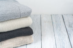 Knitted wool sweaters. Pile of knitted winter clothes on wooden background, sweaters, knitwear, space for text. Knitted wool sweaters. Pile of knitted winter stock photos
