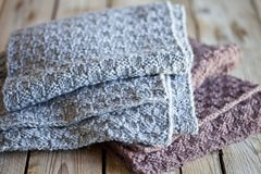 Knitted woolen grey and brown scarves stock images