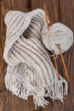 Knitted woolen scarf and skein of yarn with knitting needles Stock Photos