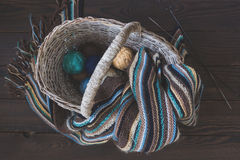Knitted woolen scarf and yarn balls in a wicker basket on a wood Royalty Free Stock Image