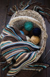 Knitted woolen scarf and yarn balls in a wicker basket on a wood Stock Photography