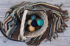 Knitted woolen scarf and yarn balls in a wicker basket on a wood Stock Images