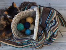 Knitted woolen scarf and yarn balls in a wicker basket on a wood Stock Photos