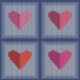 Knitted woolen seamless pattern with pink hearts in vintage blue squares. Valentine`s Day Royalty Free Stock Image