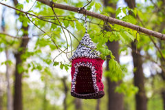 Knitted from yarns birdhouse hanging in the park. Stock Photos