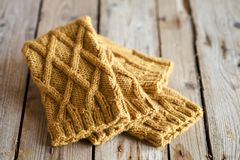 Knitted yellow leg warmers. On wooden background royalty free stock image
