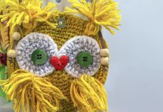 Knitted yellow owl with a nose in the form of a red heart stock image
