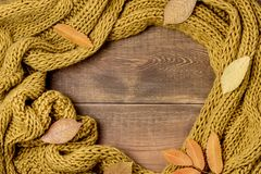 Knitted Yellow Scarf Wooden Background Copy Space. Horizontal stock photo