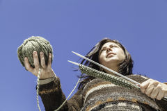 Knitter. The young woman holding a knitting equipment. Point of view form below Stock Images