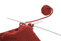 Knitting. A small ball of yarn being knitted into a cloth, shot on a white background Royalty Free Stock Image