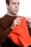 Knitting. A young man is knitting something while sitting down, isolated against a white background Stock Image