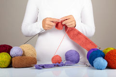 Knitting. Woman's hands with Knitting and some yarn balls Royalty Free Stock Photography