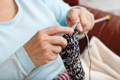 Knitting. Hands of an elder woman doing knitting at home royalty free stock image