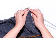 Knitting. A woman knitting with gray wool, a close-up of her hand stock images