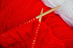 Knitting. Closeup of red knitting handcraft in progress Royalty Free Stock Photography