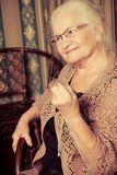 Knitting. Portrait of a smiling senior woman knitting on spokes at home. Old-fashioned style Royalty Free Stock Photos