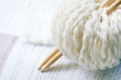 Knitting. Cream natural white yarn wool with bamboo knitting needles over pattern instructions; copy space Stock Photo