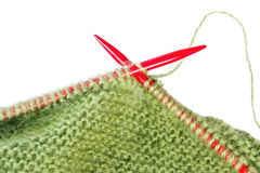 Knitting. With green fluffy wool, on red  needles.  Close-up view, over white Stock Photos