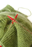 Knitting. With green wool and red needles Royalty Free Stock Image