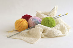 Knitting. Color balls of wool, knitting needle and unfinished scarf stock images