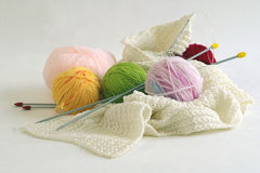 Knitting. Color balls of wool, knitting needle and unfinished scarf stock photos