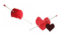 Knitting. Red knitted heart with  Eros' arrow and a skein with needle Stock Photos