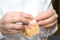 Knitting. Two hands knitting a wool dress Stock Photos