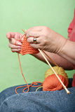 Knitting. Woman knitting with orange and yellow yarn against green background royalty free stock images