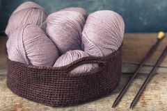 Knitting accessories needles with pink wool yarn in the crocheted basket. Toned Stock Photos