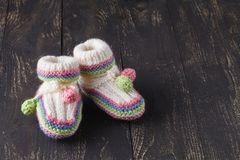Knitting baby shoes. With multicolor yarn stock photos