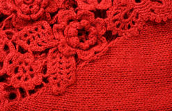 Knitting background. Red knitting background with decorative flowers royalty free stock images