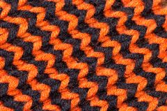Knitting. Background knitted texture. Bright knitting needles. Orange and black wool yarn for knitting stock images