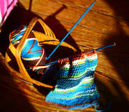Knitting Basket. A knitting basket with colorful yarn, and knitting needles, and a scarf project in process Stock Photo