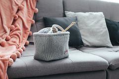 Knitting and blanket on the sofa. Knitted basket with yarn and needles on grey sofa by the warm pompon blanket and cushions. Still life photo of nordic interior Royalty Free Stock Images