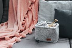 Knitting and blanket on the sofa. Knitted basket with yarn and needles on grey sofa by the warm pompon blanket and cushions. Still life photo of nordic interior Stock Photo