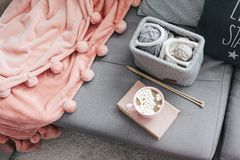 Knitting, book, cocoa and blanket on the sofa. Cocoa with marshmallows, book and knitted basket with yarn and needles on grey sofa by the warm pompon blanket and Royalty Free Stock Photography