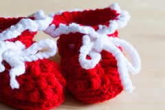Knitting. Christmas baby`s bootees, close up Royalty Free Stock Images