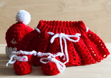 Knitting. Christmas hat, skirt, baby`s bootees, close up Royalty Free Stock Photo