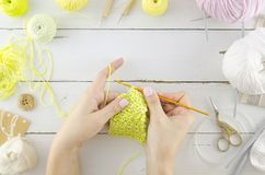Knitting concept with woman`s hands. Flat lay wooden desk with tools and accessories. Holding knitting needles royalty free stock photos