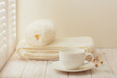 Knitting and a cup on a light wooden background near a window wi. Th shutters Royalty Free Stock Photo