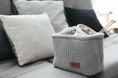 Knitting and cushions on the sofa. Knitted basket with yarn and needles on grey sofa by cushions. Still life photo of nordic interior details. Cosy place in Royalty Free Stock Image
