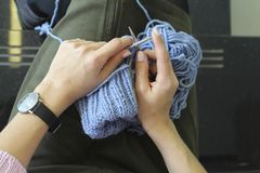 Knitting. Female hands with knitting needles. Top view. Close-up. stock images